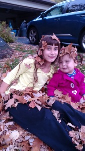 Shira and Eliana covered with leaves